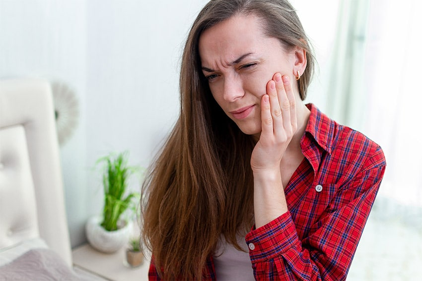young woman in red flannel shirt with jaw pain
