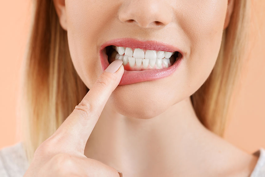 closeup of a woman pointing to her red, inflamed gums